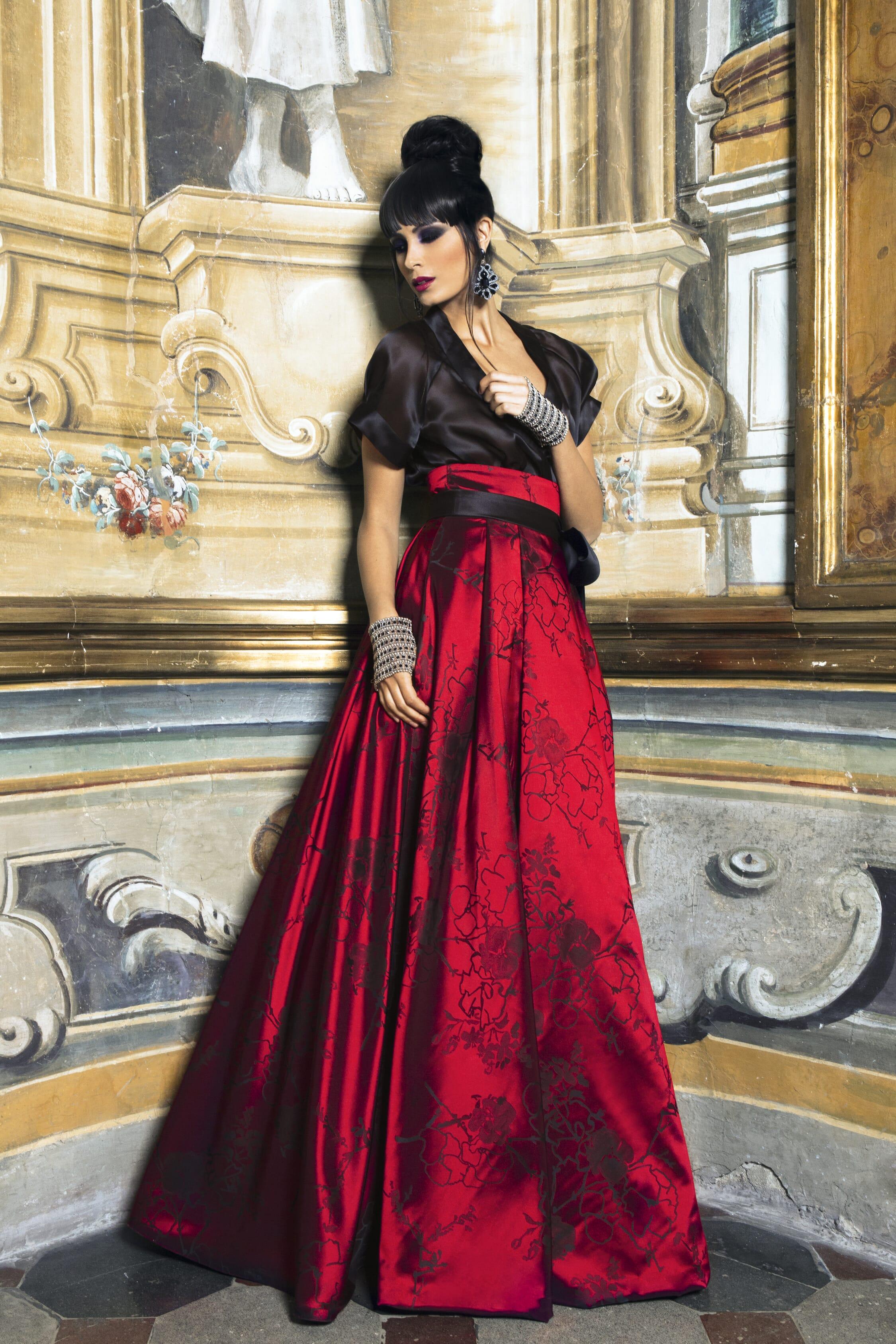 Abito da cerimonia con blusa in organza nera trasparente e gonna ampia rossa con motivi neri e cintura alta in vita