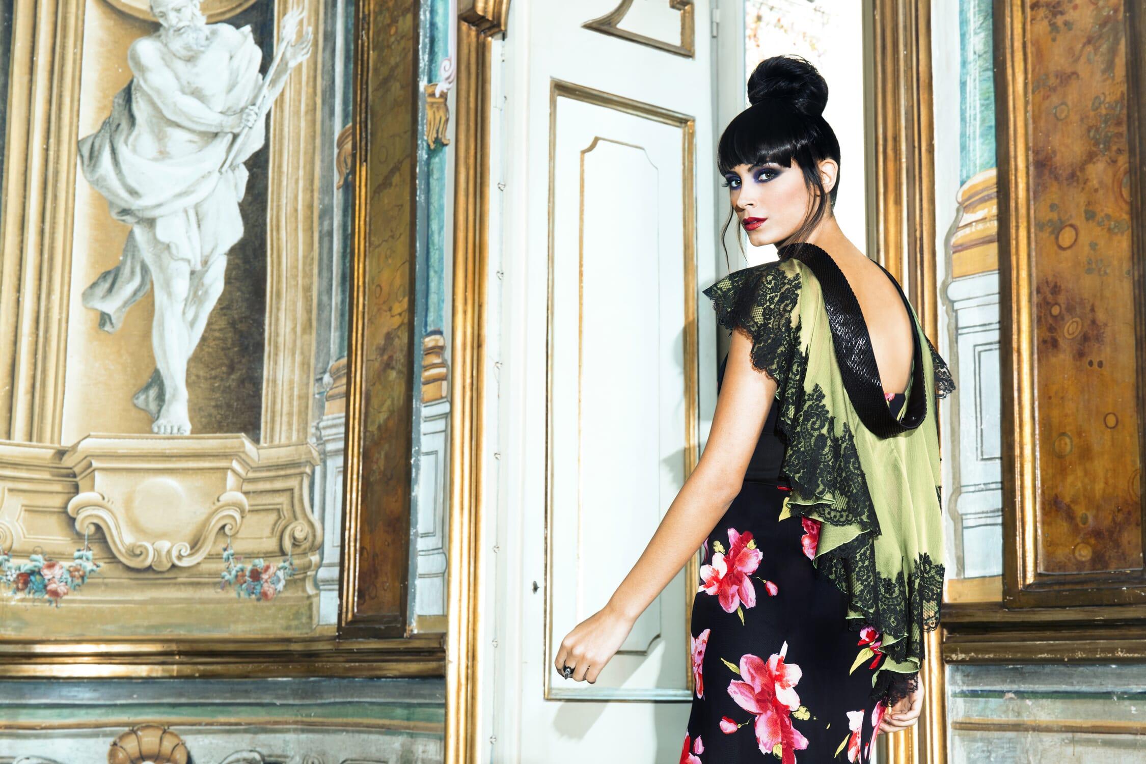 Foto vista posteriore di abito lungo da sera in tessuto nero con fiori a contrasto e applicazione di mantellina lavorata sui bordi che lascia la schiena un pò scoperta.