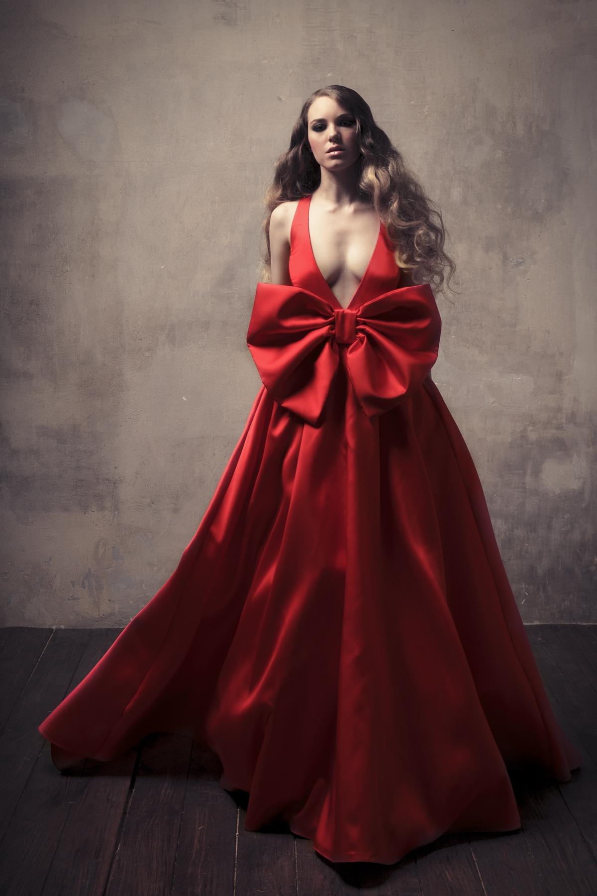 Abito da sera rosso con profondo scollo, in seta liscia con grande fiocco sul davanti.